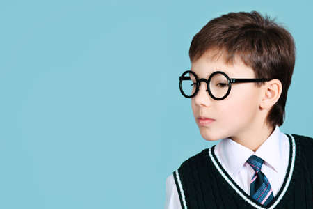 Educational theme: portrait of a schoolboy. Studio shot over grey background. photo