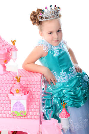 Beautiful little girl in princess dress playing with her toy castle. Isolated over white background. photo