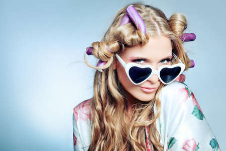 Portrait of a pretty girl with curlers in her hair. Over grey background. photo