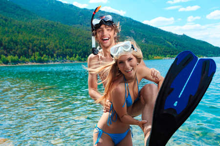 Happy young couple with snorkelling gear standing on a sea beach. Stock Photo - 8835188