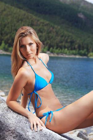 Beautiful young woman in bikini posing on a sea beach. photo