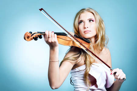 Beautiful young woman playing her violin with expression. Over grey bakground. Stock Photo