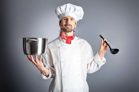 boiling: Portrait of a man cook holding a saucepan and ladle. Shot in a studio over grey background.