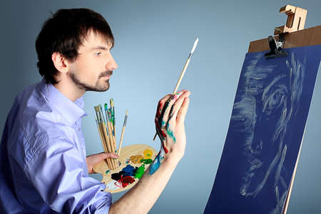 artist: Portrait of an artist painting on easel. Shot in a studio.