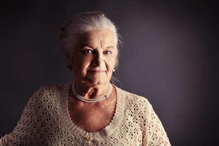 Portrait of a smiling senior woman. Studio shot over grey background. photo