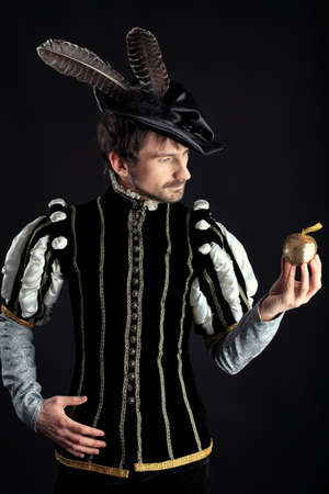 Portrait of a handsome man grandee in 16th century costume. Shot in a studio over black background.
