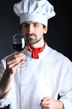Portrait of a man cook holding a glass of red wine. Shot in a studio over black background. Stock Photo - 8835210
