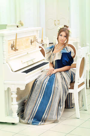 Beautiful young woman in medieval era dress playing the piano. Stock Photo - 8835237