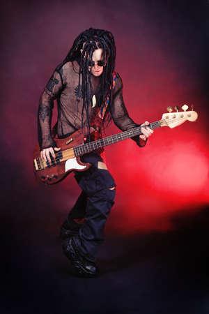 dreadlock: Heavy metal musician  is playing electrical guitar. Shot in a studio.