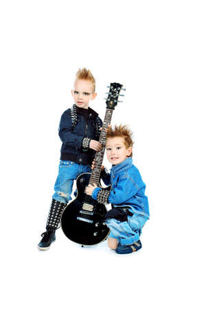 hardrock: Shot of two little boys posing in costumes of rock musicians with electric guitar. Isolated over white background.