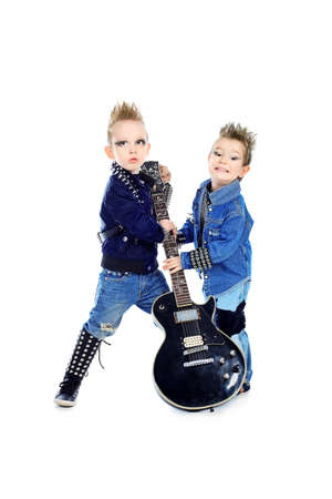 Shot of two little boys posing in costumes of rock musicians with electric guitar. Isolated over white background. photo