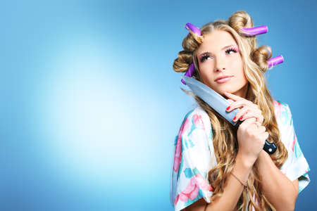 Portrait of a pretty girl with curlers in her hair holding a knife. Over grey background. Stock Photo - 8835353