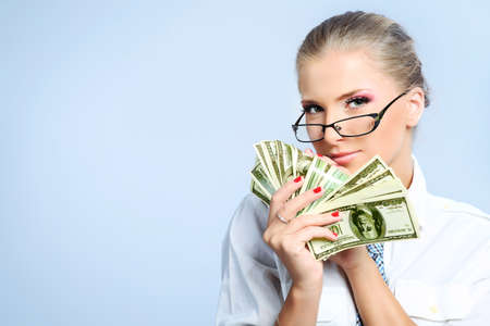 Beautiful businesswoman holding money. Studio shot over grey background. Stock Photo - 8835345
