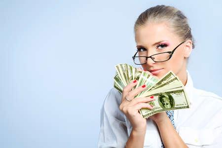 rich: Beautiful businesswoman holding money. Studio shot over grey background. Stock Photo