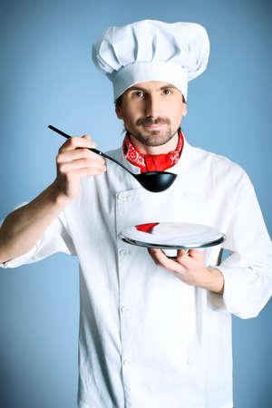 italienisches essen: Portr�t eines Mannes Kochen holding eine Platte und Suppenkelle. Gedreht in einem Studio �ber grau hintergrund.