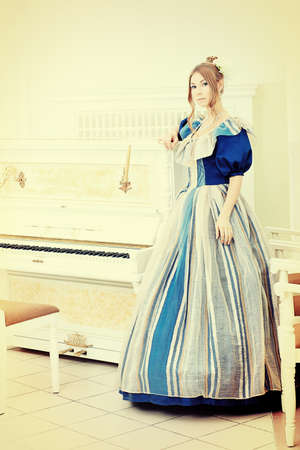 Beautiful young woman in medieval era dress playing the piano. photo