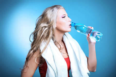 grey water: Shot of a sporty young woman drinking water after training. Active lifestyle, wellness.