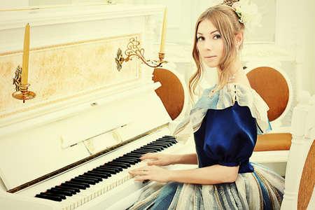 vestido medieval: Joven y bella mujer en traje de �poca medieval, tocando el piano.