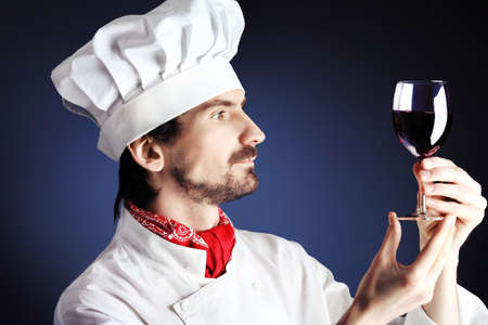 viniculture: Portrait of a man cook holding a glass of red wine. Shot in a studio over black background. Stock Photo