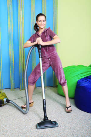 Woman housewife with a vacuum cleaner at home. photo