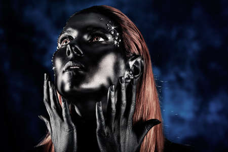 Portrait of an artistic woman painted with black color and spangled. Body painting project. Jewellery. photo