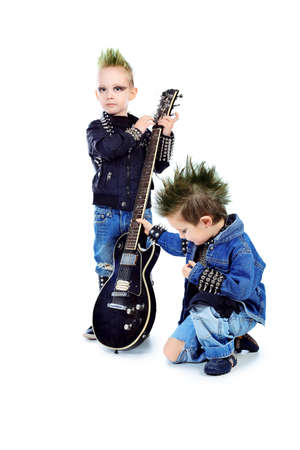 Shot of two little boys posing in costumes of rock musicians with electric guitar. Isolated over white background. Stock Photo - 8935196