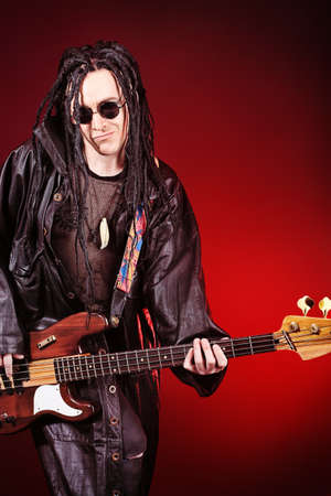 harmonist: Heavy metal musician  is playing electrical guitar. Shot in a studio.