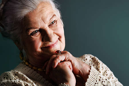 abuela: Retrato de una mujer sonriente senior. Studio dispar� sobre fondo gris.