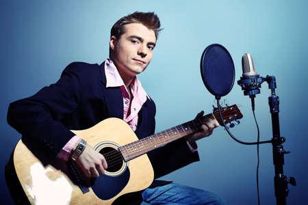 estudio de grabacion: Joven est? jugando en una guitarra en el estudio, el estilo de rock and roll.