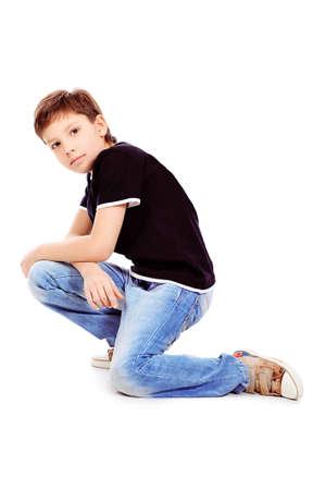 teenager thinking: Retrato de un ni�o lindo a�o 9 sentado en un piso. Aislados sobre fondo blanco.