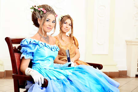 costume ball: Two beautiful women in medieval era dresses.