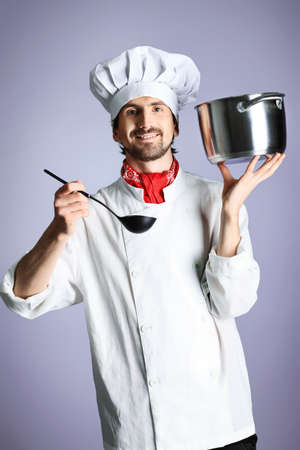Portrait of a man cook holding a saucepan and ladle. Shot in a studio over grey background. Stock Photo - 8938272