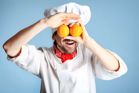 toque blanche: Portrait of a man cook holding oranges. Shot in a studio over grey background.