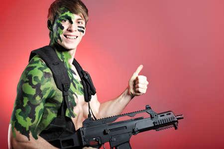 commando: Shot of a conceptual soldier painted in khaki colors. Studio shot.