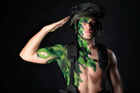 salut: Shot of a conceptual soldier painted in khaki colors. Studio shot over black background. Stockfoto