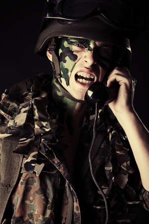 Shot of a soldier talking by radio station. Studio shot over black background. photo