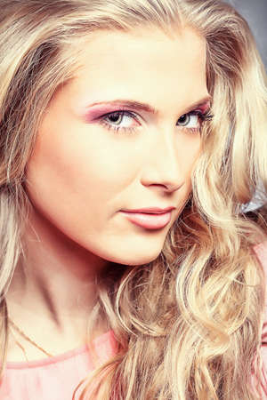 Beautiful young woman with long blonde hair posing over grey background. Stock Photo - 9006762