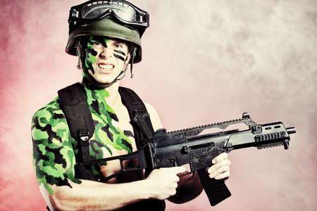 Shot of a conceptual soldier painted in khaki colors. Studio shot. photo