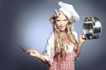 Beautiful blonde woman housewife holding pan. Studio shot over grey background. Stock Photo - 9006494
