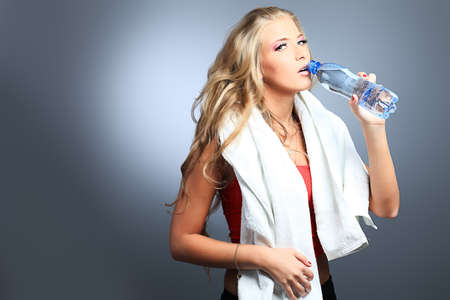 Shot of a sporty young woman drinking water after training. Active lifestyle, wellness. photo