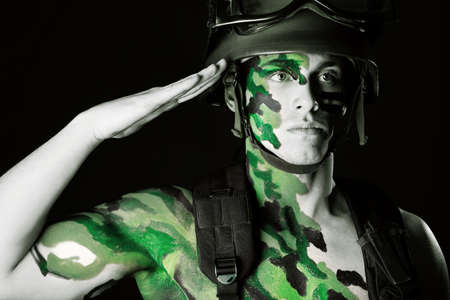 khaki: Shot of a conceptual soldier painted in khaki colors. Studio shot over black background. Stock Photo
