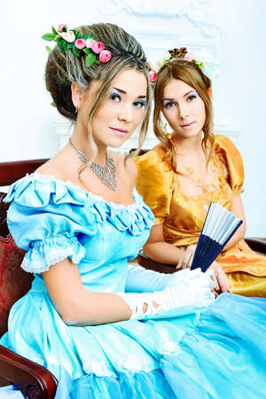 Two beautiful women in medieval era dresses. photo