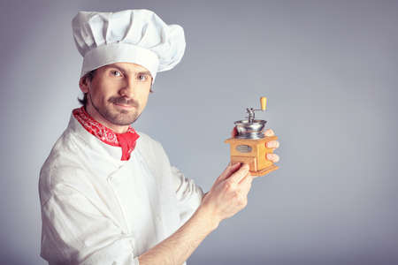 Portrait of a man cook holding coffee grinder. Shot in a studio over grey background. photo