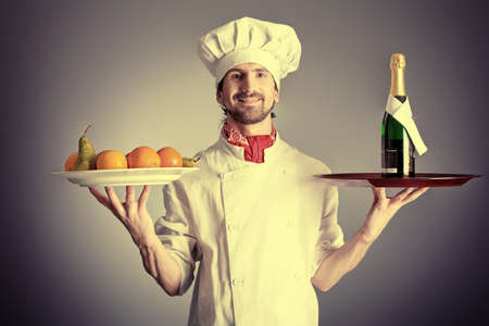 Portrait of a man cook holding a bottle of champagne and fruits. Shot in a studio over grey background. photo