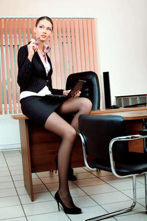 stern: Attractive business woman is working at the office.