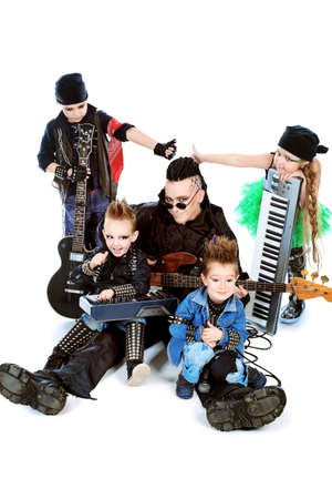 harmonist: Heavy metal musician  with a group of stylish children  Shot in a studio  Isolated over white background  Stock Photo