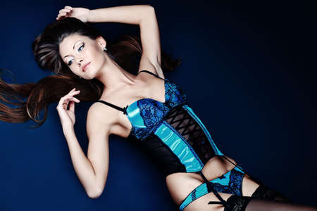 Shot of an attractive young woman in sexual lingerie, over black background.  Stock Photo - 9073907