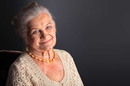 Portrait of a smiling senior woman. Studio shot over grey background. photo