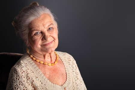 one senior adult woman: Retrato de una mujer sonriente senior. Studio dispar� sobre fondo gris.