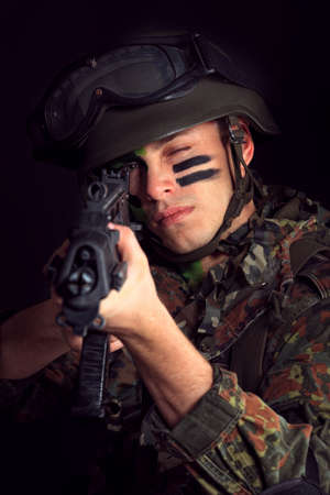 face guard: Shot of a conceptual soldier painted in khaki colors. Over black background.